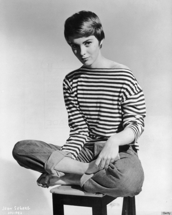 circa 1965: Promotional portrait of American actor Jean Seberg (1938 - 1979) sitting barefoot and cross-legged on a stool, wearing rolled blue jeans and a French-striped sailor jersey pulled off one shoulder. (Photo by Hulton Archive/Getty Images)